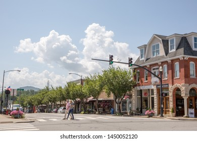 BREVARD, NC (USA) - July 7, 2019:  A couple crosses Main Street at the intersection of Main and Broad Streets in downtown Brevard.
