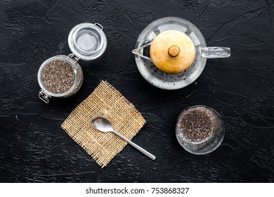 Brew chia seeds. Jar with seeds, scoop, bowl, tea pot with hot water. Black background top view.