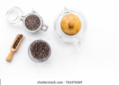 Brew chia seeds. Jar with seeds, scoop, bowl, tea pot with hot water. White background top view copyspace