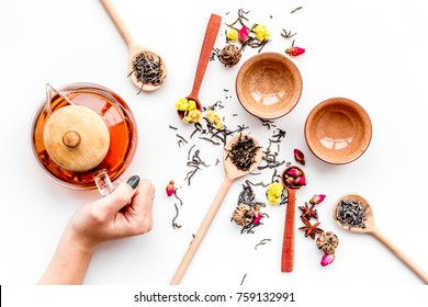 Brew tea with flowers and spices. Pour the tea. Hand hold tea pot on white background top view
