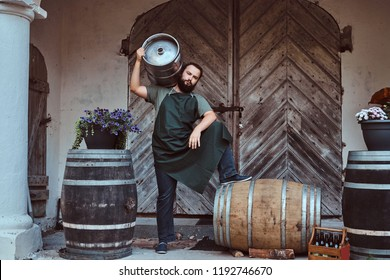 Brewer in apron holds barrel with craft beer at brewery factory.