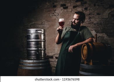Brewer in apron standing near barrels and drinks craft beer at old brewery factory.