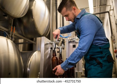 Brewer filling beer in bottle from tank at brewery