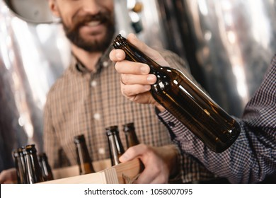 Brewer holds empty beer bottle in hand. Stages of brewing production. Process of beer manufacturing. Quality control. Brewing.