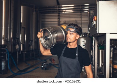 Brewer with large metal container at brewery factory. Young man working at warehouse in brewery holding a metal beer barrel.