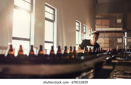 Brewer looking at conveyor with beer bottles. Young man supervising the manufacturing process of beer at brewery factory.