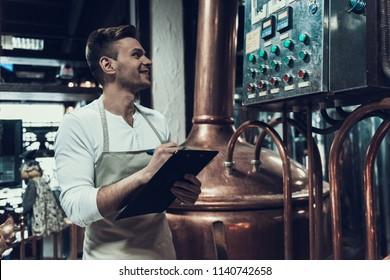 Brewer Standing near Apparatus in Modern Brewery. Professional Brewer. Fermenting Beer. Metal Tank. Work in Brewery. Craft Beer. Inspector at Beer Factory. Modern Beverage Industry.