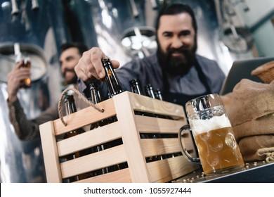 Brewers are testing beer. Beer mug on background of brewers. Brewing. Brewery. Beer crafting. Adult bearded men try craft beer.