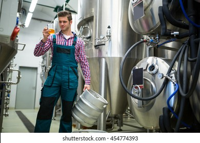 Brewery holding keg and testing beer at brewery factory
