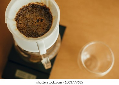Brewing aromatic fresh coffee in paper filter closeup in pour over on scale. Alternative coffee brewing closeup. Barista making filter coffee on brown background