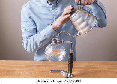 brewing coffee siphon. step by step cooking instructions. pouring siphon into the flask from the kettle of hot water