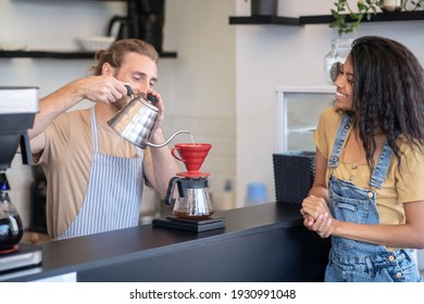 Brewing method. Happy male barista standing behind bar making coffee with pourover and watching long haired woman