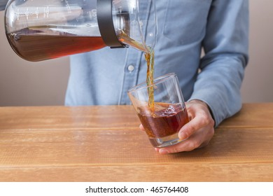 brewing process step by step. Barista pouring cold coffee brewing in a glass. The culmination of the process