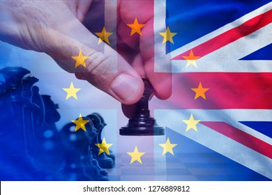 Brexit concept with hand making a chess move and flags of European Union and The United Kingdom combined. Background theme of strategy in european politics