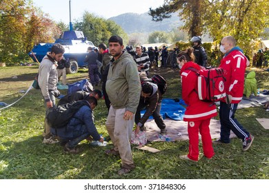BREZICE, SLOVENIA: OCTOBER 28, 2015: Immigrants and refugees from Middle East and North Africa at Brezice camp receiving water from Red Cross volunteers. .