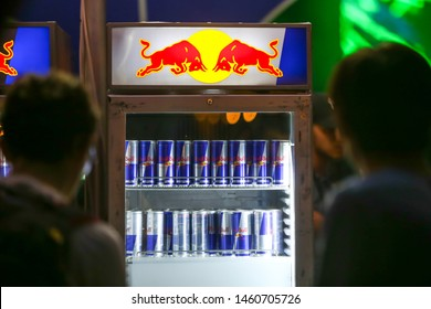 Brezje, Croatia - 19th July, 2019 : People on the Red bull bar with fridge full of Red Bull energy drink on the Forestland, ultimate forest electronic music festival located in Brezje, Croatia.