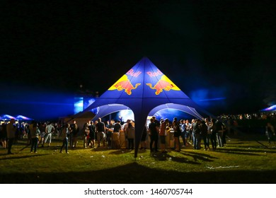 Brezje, Croatia - 19th July, 2019 : People on the Red bull tents with a bar on the Forestland, ultimate forest electronic music festival located in Brezje, Croatia.