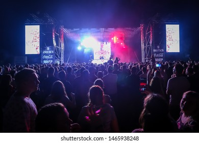 Brezje, Croatia - 20th July, 2019 : Rear view of the crowd with main stage in the background on the Forestland, ultimate forest electronic music festival located in Brezje, Croatia.