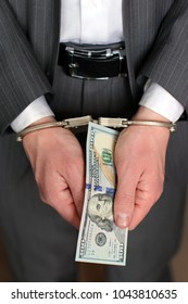 Bribe conception. Man in handcuffs hold american dollars in arm.