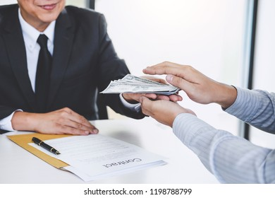 Bribery and corruption concept, bribe in the form of dollar bills, Businessman giving money while making deal to agreement a real estate contract.