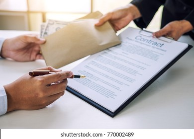 Bribery and corruption concept, bribe in the form of dollar bills, Businessman giving money in the envelope while making deal to agreement a real estate contract and financial corporate.
