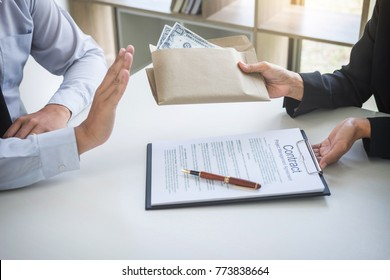 Bribery and corruption concept, Businessman refusing receive money in the envelope to agreement contract, A bribe in the form of dollar bills.