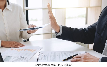 Bribery and corruption concept, senior businessman manager refusing receive money in the envelope to agreement contract, A bribe in the form of dollar bills.