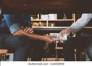 Bribery, Hands passing money under table, Corruption and bribery concepts.
