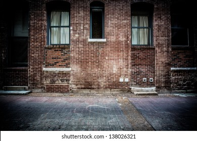 A brick alleyway with concrete walkway. Old windows and doors made of metal and glass with stairs and steps