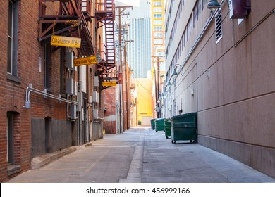 Brick alleyway with dumpsters and fire escape and copy space.