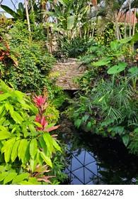 Brick bridge at a vibrant botanical garden.