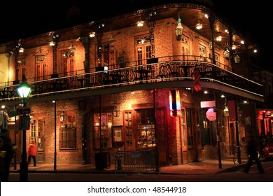 Brick building with balcony on the corner of St. Peter and Bourbon Streets at night in the French Quarter of New Orleans, LA