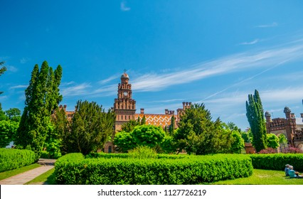 brick building of the university against the background of blue sky and green trees