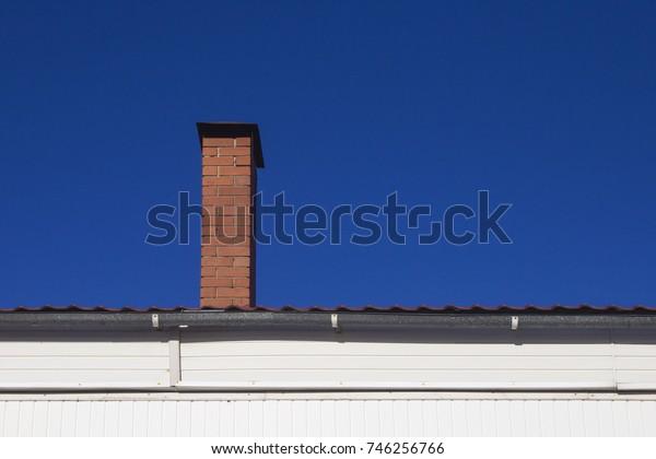 brick chimney against the blue sky