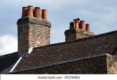 Brick chimneys on clayed old roof with cloudy sky in background
