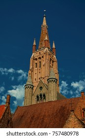 Brick church steeple, roofs and blue sky in Bruges. With many canals and old buildings, this graceful town is a World Heritage Site of Unesco. Northwestern Belgium. Retouched photo.