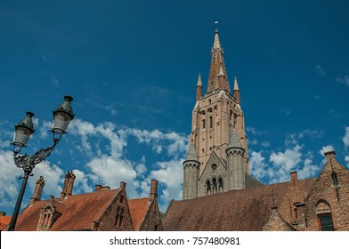 Brick church steeple, roofs and public lamp contrasting with blue sky in Bruges. With many canals and old buildings, this graceful town is a World Heritage Site of Unesco. Northwestern Belgium.