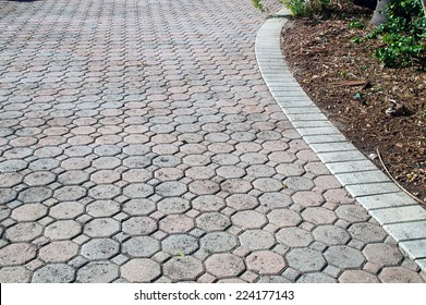 A brick driveway in bonita springs florida composed of octagon and square shaped bricks stretches off into the distance bordered with white bricks.