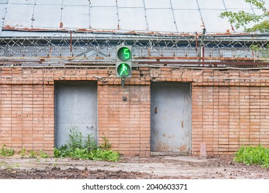 Brick fence with barbed wire of the prison with trafficlight.