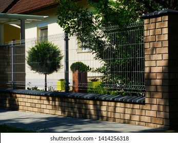 Brick fence post pier with ceramic cap stone. detail with painted wire mesh grille fence panels. house in the background with beautiful front yard. shrubs and plants. home ownership & security concept