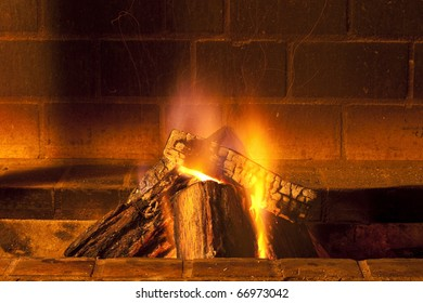 brick fireplace with large pieces of wood burning giving warmth