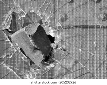 Brick got stuck in a window with reinforced glass in black and white as a symbol of vandalism