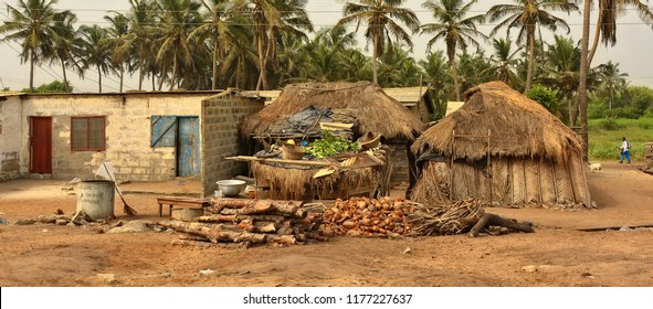 Brick house & barracks with thatched roof with household items in a yard. Rural lifestyle of West Africa. Traditional way of life in developing countries. Ghana, village near Atoko - December 31,2016