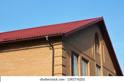 Brick house construction with metal rooftop and gutter.
