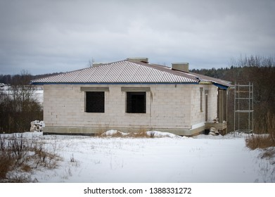Brick House construction site. Building construction silicate brick house. Unfinished Home Construction with roof in winter