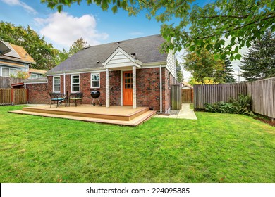 Brick house exterior with walkout wooden deck and patio area with barbecue
