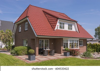 brick house with red roof and patio, garden