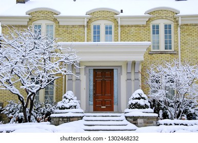 brick house with snow covered steps and shrubbery