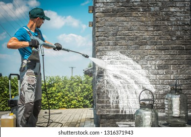 Brick House Wall Pressure Washing with Special Cleaning Detergent. Caucasian Men in His 30s. Taking Care of the Building Elevation.