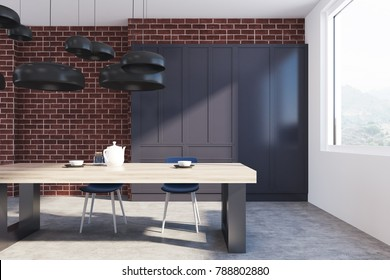 Brick kitchen interior with a concrete floor, a massive wooden table, and black chairs. A black cupboard in the background. Close up 3d rendering mock up
